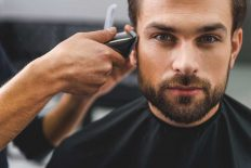 man having his hair cut - using clippers to tidy his side burns