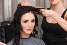 brunette girl having her hair styled with curling tong